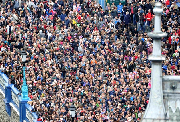 Crowds gather at Tower Bridge on the banks of the River Thames to view the spectacle of the Thames Diamond Jubilee Pageant in London on June 3, 2012. Queen Elizabeth II was to sail on a ceremonial barge down the Thames on Sunday at the centre of a 1,000-boat pageant to mark her diamond jubilee, although heavy rain threatened to spoil the party. AFP PHOTO / POOL / PAUL HACKETTPAUL HACKETT/AFP/GettyImages